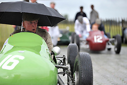 © Licensed to London News Pictures. 17/09/2011. GOODWOOD, UK. A driver shelters from a sudden shower. The Goodwood Revival at Goodwood in West Sussex today (17 September 2011). The revival is the world's largest historic motor race meeting, which relieves the 'glorious' days of the race circuit. Competitors and enthusiasts all dress in period fashion to enhance the experience. Photo credit : Stephen Simpson/LNP