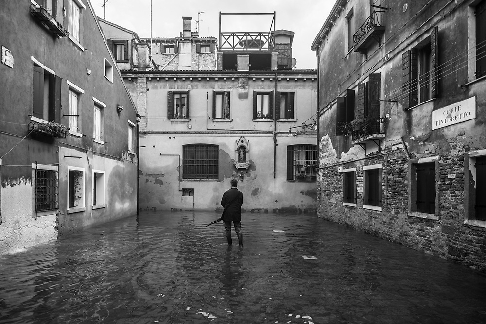 Venice, Italy. 29 October, 2018.  A man walks in a flooded small square to reach his home during the high tide on October 29, 2018, in Venice, Italy. This is a selection of pictures of different areas of Venice that the press has not covered, were resident live and every year they have to struggle with the high tide. Due to the exceptional level of the 'acqua alta' or 'High Tide' that reached 156 cm today, Venetian schools and hospitals were closed by the authorities, and citizens were advised against leaving their homes. This level of High Tide has been reached in 1979. © Simone Padovani / Awakening / Alamy Live News