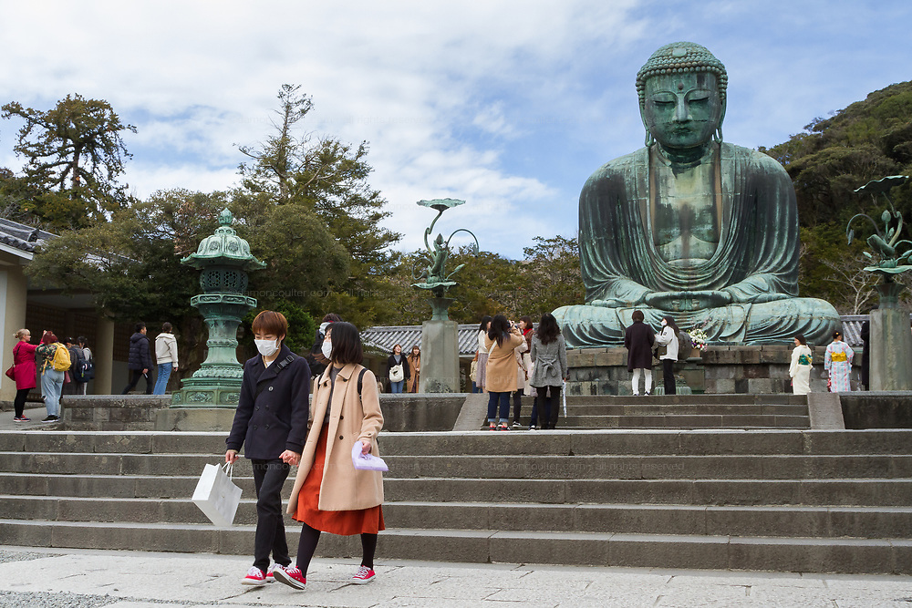 Tourists , some wearing face masks for protection against the Coronavirus (COVID-19) visit the the Daibutsu (Big Buddha) at Kotokuin Temple, Kamakura, Kanagawa, Japan. Thursday March 5th 2020
