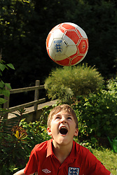 A boy playing football in the garden MODEL RELEASED