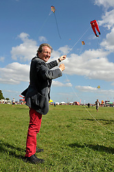 © Licensed to London News Pictures. 31/08/2013. Bristol, UK.  The Mayor of Bristol, George Ferguson, flys a kite in the shape of his trademark red trousers at The Bristol International Kite Festival at Ashton Court Estate.  Guest flyers from across the world have flown in specially to create a  spectacle of both special shaped kites, and team displays. 31 August 2013.<br /> Photo credit : Simon Chapman/LNP