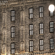 Side of an old Manhattan brick building with the afternoon sun reflecting off a window