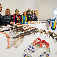 021413       Brian Leddy<br /> Rydell Curley shows off items in the Dine College archive, including an 18th century Sioux war shirt made with real human hair on Friday. The college recently completed a new building to house and preserve it's extensive archive collection.
