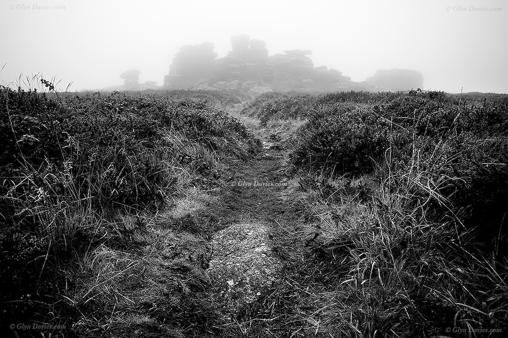 The imposing granite rock mass of Kenidjack Tor looms out of the fog on a damp Autumn morning on the Cornish moorlands, from where you can normally see the Atlantic Ocean on three sides.