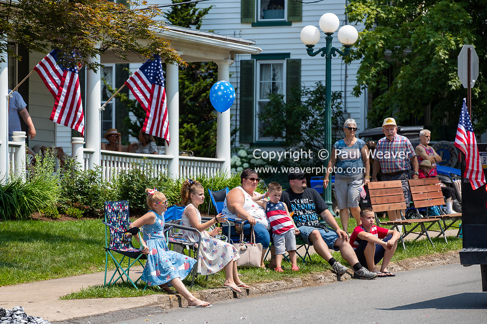People sit along the street watching the Independence Day parade in Millville, Pennsylvania on July 5, 2021.