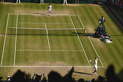 © London News Pictures. 07/07/2013 . London, UK. Andy Murray (foreground) celebrates after his men's singles final victory over Novak Djokovic (background) of Serbia at the Wimbledon Lawn Tennis Championships, becoming the first British male to win the tournament in 77 years. Photo credit: Mike King/LNP