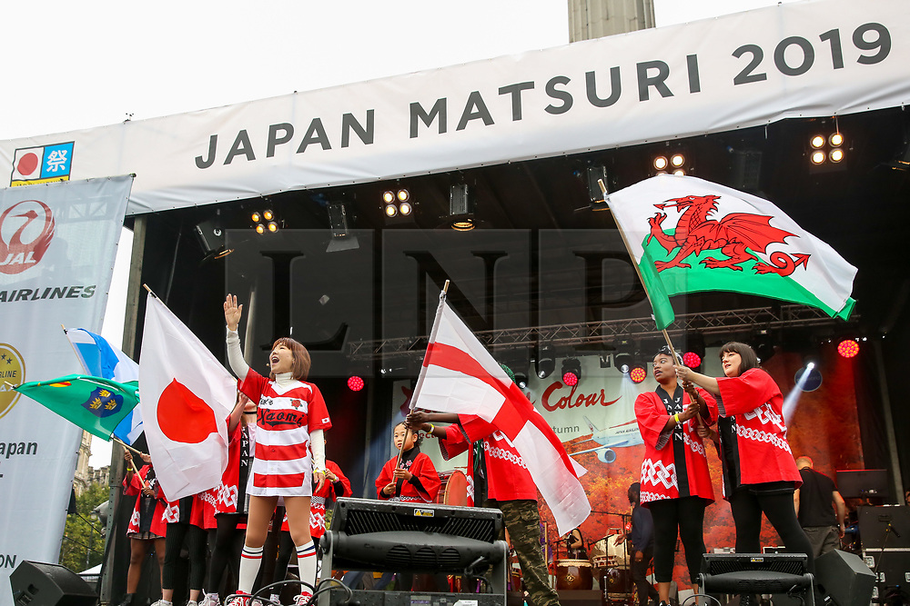 """© Licensed to London News Pictures. 29/09/2019. London, UK. Performers performs a """"Rugby World Cup"""" dance waving flags of Japan, England, Scotland and Wales during the annual Japan Matsuri festival of Japanese music, food and culture in Trafalgar Square. The concept of the theme this year is """"Future generations"""". Photo credit: Dinendra Haria/LNP"""
