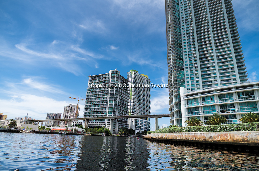 Miami Metro elevated train tracks pass between condominium buildings on the banks of the Miami River in downtown Miami, Florida. WATERMARKS WILL NOT APPEAR ON PRINTS OR LICENSED IMAGES.