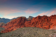 A band of cirrus clouds turns pink at sunset over the Calico Hills in the Red Rock Canyon Conservation Area in Nevada. The Calico Hills are made up of Aztec Sandstone, fossilized sand dunes that were laid down during the early Jurrasic Period 180-190 million years ago.