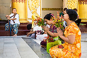 15 JUNE 2013 - YANGON, MYANMAR:  Women pray at Shwedagon Pagoda. Shwedagon Pagoda is officially known as Shwedagon Zedi Daw and is also called the Great Dagon Pagoda or the Golden Pagoda. It is a 99 meter (325 ft) tall pagoda and stupa located in Yangon, Burma. The pagoda lies to the west of on Singuttara Hill, and dominates the skyline of the city. It is the most sacred Buddhist pagoda in Myanmar and contains relics of the past four Buddhas enshrined: the staff of Kakusandha, the water filter of Koṇāgamana, a piece of the robe of Kassapa and eight strands of hair from Gautama, the historical Buddha. Burmese believe the pagoda was established as early ca 540BC, but archaeological suggests it was built between the 6th and 10th centuries. The pagoda has been renovated numerous times through the centuries. Millions of Burmese and tens of thousands of tourists visit the pagoda every year, which is the most visited site in Yangon. PHOTO BY JACK KURTZ