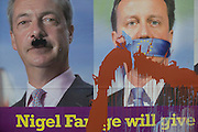 Splashed paint drips down an anti-EU membership 'UK Independence Party's (UKIP) political billboard shows leader Nigel Farage (with daubed Hitler moustache) and a gagged Prime Minister David Cameron, silent against a bullying European Union, seen in East Dulwich - a relatively affluent district of south London. The ad is displayed before European elections on 22nd May.