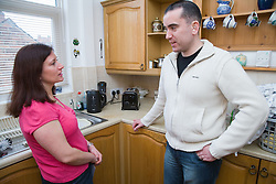 Man with a hearing impairment talking to his sister in the kitchen,