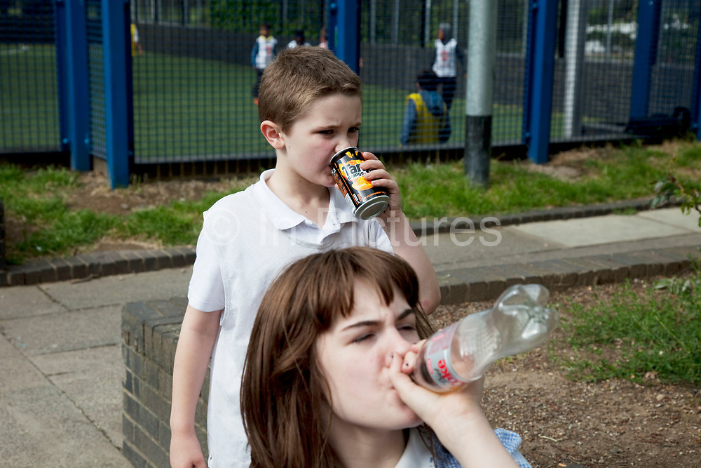 Brother and sister Georgia Ryan  (11) and Kiefer (8) drinking fizzy drinks. Hanging around in the Harvist Estate, Arsenal, North London. Louise is on various benefits to help support her family income, and housing, although recent government changes to benefits may affect her family drastically, possibly meaning they may have to move out of London. Louise Ryan was born on the Wirral peninsula in 1970.  She moved to London with her family in 1980.  Having lived in both Manchester and Ireland, she now lives permanently in North London with her husband and two children. Through the years Louise has battled to recover from a serious motorcycle accident in 1992 and has recently been diagnosed with Bipolar Affective Disorder. (Photo by Mike Kemp/For The Washington Post)