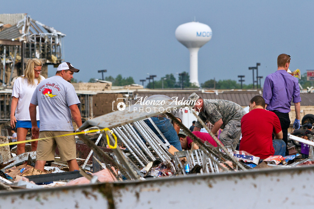 People search through debris that was once the 7-Eleven Store near the Moore Medical Center after a tornado tore through Moore, Okla. on May 20, 2013.  (Photo copyright © 2013 Alonzo J. Adams)