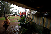 Sydney and Tiaan (12 years old) and Reynard (14 years old) enter in the tent to run away from the rain. Rainy days remember to the family how was living in a proper house pefore loosing everything.