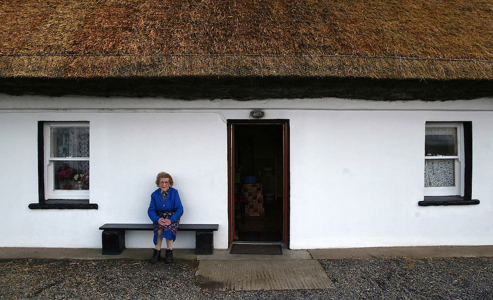 Eighty-four-year old Lily Quinn sits in front of the thatched roof home in Bundoran, County Donegal, Ireland, where she was born and raised. The roof has been replaced numerous times and the exterior has had a paint job, but the two-room house, heated by a peat fireplace, otherwise  remains untocuhed since her youth.