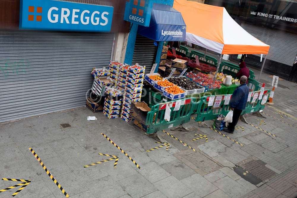 The UK Chancellor Rishi Sunak has said it is very likely the UK is in a significant recession due to the Coronavirus pandemic lockdown, as figures show the economy contracting at the fastest pace since the financial crisis. And in the face of continued lockdown on the high street such as here on the Walworth Road in south London, a lone shopper buys essential fruit and veg at East Street market where customers must observe social distancing with marks on the pavement on 13th May 2020, in London, England.