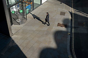 While office workers largely remain at home in accordance to government Covid guidelines and individual corporate policies, a socially distanced company employee walks towards the one-way revolving doorway entrance in the City of London, the capital's financial district, during the third lockdown of the Coronavirus pandemic, on 9th March 2021, in London, England.
