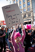 """San Francisco, USA. 19th January, 2019. A young girl wearing a pink pussy hat carries a sign reading: Without Hermione Harry would have died in Book One!"""" at the Women's March San Francisco. Credit: Shelly Rivoli/Alamy Live News"""