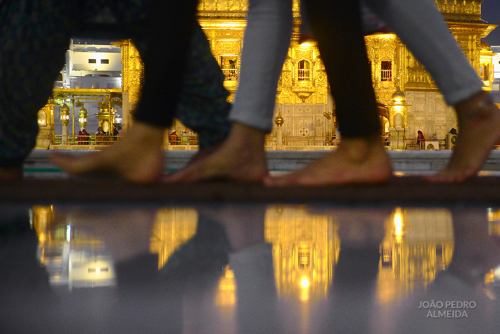 Pilgrims walking barefoot at Golden Temple, as no shoes are allowed.