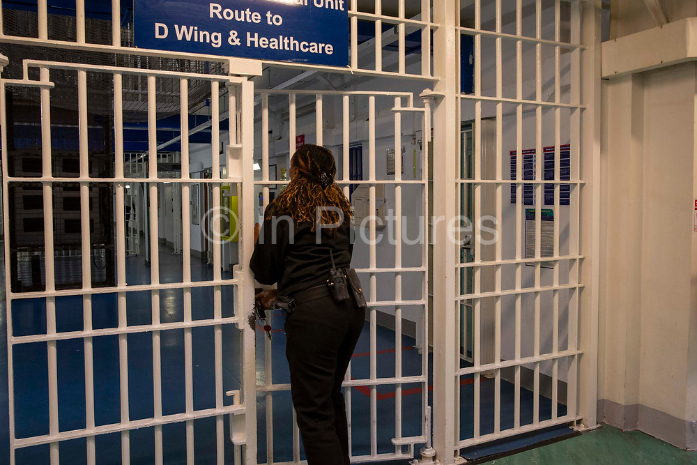 A female Prison Officer locks the metal gate entrance to D Wing and Healthcare Wing of Her Majesty's Prison Pentonville, London, United Kingdom.