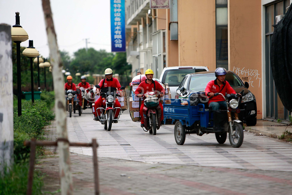 """Courriers drive out on their motorbikes and scooters to deliver shopping orders at one of the Yihaodian neighborhood distribution centers in Shanghai, China on 23 August, 2011. As online supermarkets is attracting a rapidly increasing number of young consumers, especially women, U.S. giant Walmart has acquired a minority stake in Yihaodian, or """"The Store"""", a young but very successful E-Commerce company that sells and delivers everything from food, daily household  items, electronics, and clothing."""