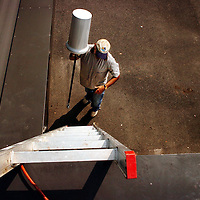 """Eric """"Zonker"""" Harris carries a large transmitter onto the roof of The Pilot newspaper in Southern Pines, N.C., Tuesday, July 11, 2006. The newspaper is going to provide free wireless internet in downtown Southern Pines, N.C."""