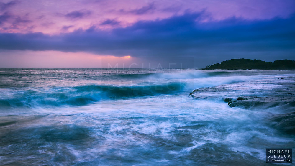 Surf breaks on rocks at Yamba, while the sun disappears behind low cumulus clouds. <br /> <br /> Code: WANNR0001<br /> <br /> Limited Edition Print
