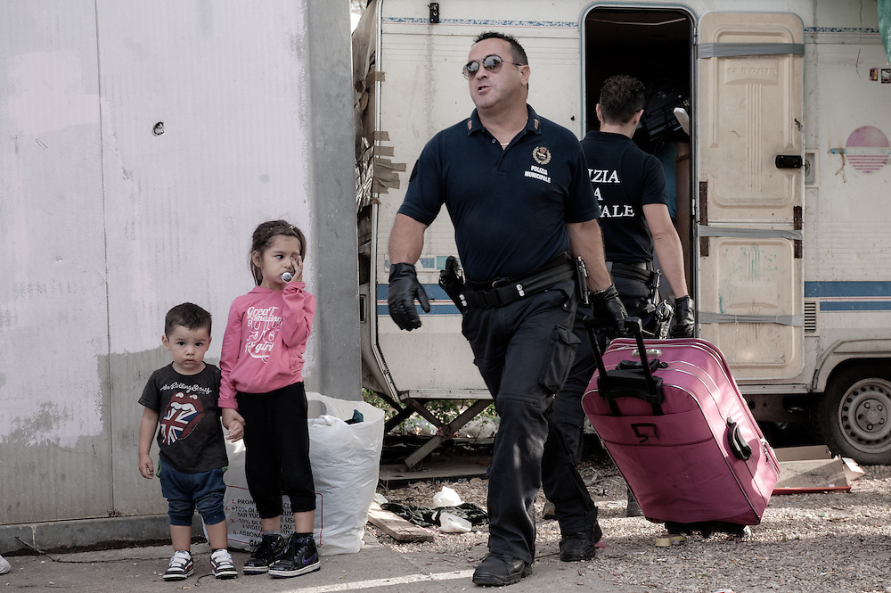 Rome, Italy - 28 September 2012: a policeman helps a romani family to move their stuff from a caravan minutes before it's destroyed by bulldozers during the forced eviction of the Tor de' Cenci camp. All major human rights associations agree that the forced eviction has been conducted in violation of the international standards on evictions and no valid housing alternative has been given to the residents.