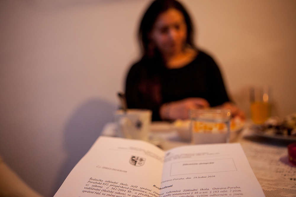 """Volunteer and Roma activist Jolana Smarhovycova (in the back) with a paper with a """"decision"""" from one of the schools where the son Richard (6) of Andrea Danova (26) was not accepted (Czech: """"se neprijma"""") for the 1st year to a mainstream school in Ostrava. During a meeting with volunteers and mothers with their children for consultation and data collection regarding school enrolments in Ostrava. The meeting was in a volunteers flat."""