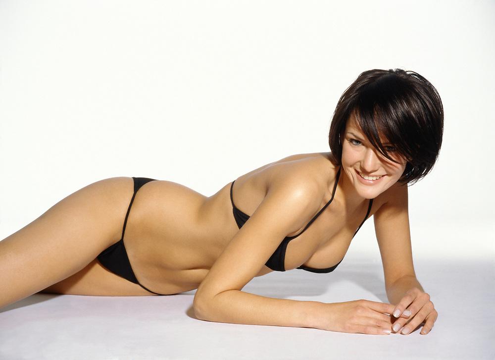 Happy woman laying down on a white background wearing a black bikini