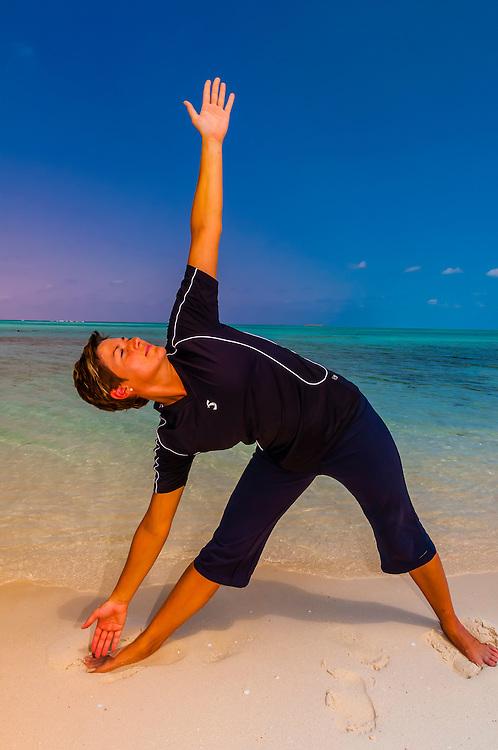 Woman doing yoga on the beach, Serenity Bay,  Castaway Cay, Disney's private island, The Bahamas