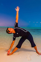 Woman doing yoga on the beach, Serenity Bay,  Castaway Cay, Disney's private island, The Bahamas