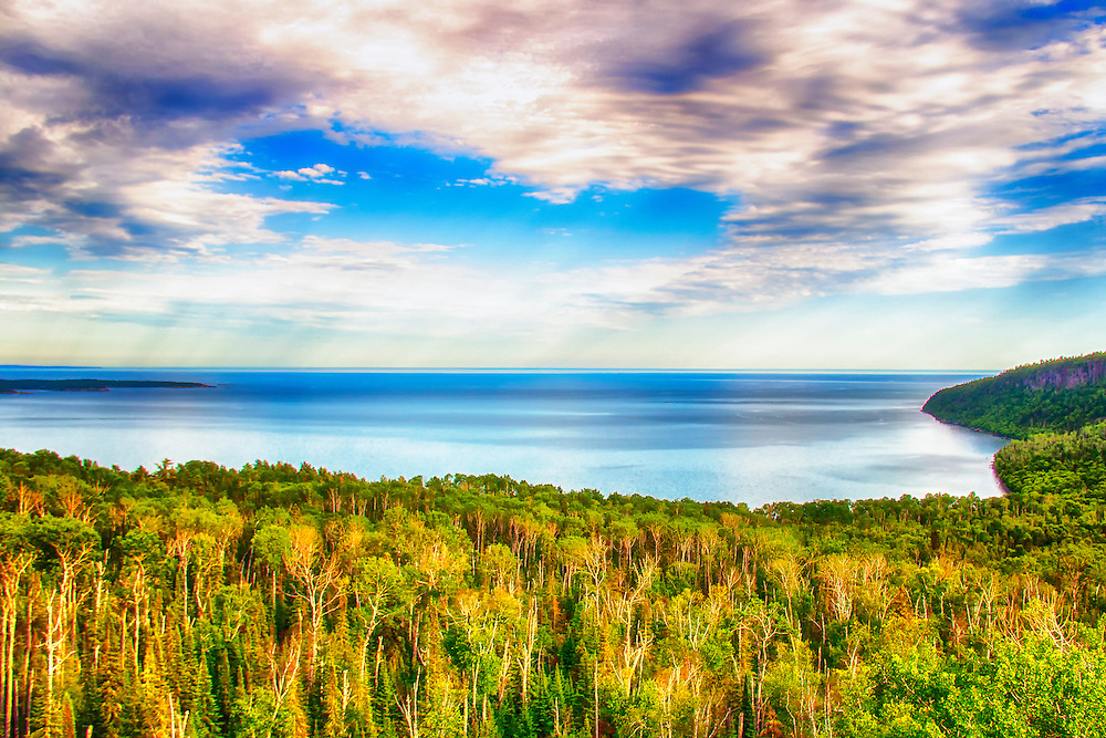 Taken on the Minnesota side of Lake Superior about 10 miles from the Canada border. The heavenly skies frame this vibrant wooded waterscape vista looking across the great lake.<br /> <br /> Lake Superior is the largest of the five traditionally demarcated Great Lakes of North America. It is bounded to the north by the Canadian province of Ontario and the U.S. state of Minnesota, and to the south by the U.S. states of Wisconsin and Michigan. It is generally considered the largest freshwater lake in the world by surface area. It is the world's third-largest freshwater lake by volume.<br /> <br /> The lake is fed by over 200 rivers. The largest include the Nipigon River, the St. Louis River, the Pigeon River, the Pic River, the White River, the Michipicoten River, the Bois Brule River and the Kaministiquia River. Lake Superior drains into Lake Huron by the St. Marys River.<br /> <br /> Over 80 species of fish have been found in Lake Superior. Species native to the lake include: bloater, brook trout, burbot, cisco, lake sturgeon, lake trout, lake whitefish, longnose sucker, muskellunge, northern pike, pumpkinseed, rock bass, round whitefish, smallmouth bass, walleye, white sucker and yellow perch. In addition, many fish species have been either intentionally or accidentally introduced to Lake Superior: atlantic salmon, brown trout, carp, chinook salmon, coho salmon, freshwater drum, pink salmon, rainbow smelt, rainbow trout, round goby, ruffe, sea lamprey and white perch.