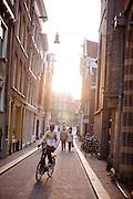 Een fietser rijdt door een smalle straat in Amsterdam.<br /> <br /> A cyclist in downtown Amsterdam