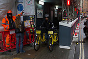 An Ofo employee pushes two rental bikes along a street, 24th January 2018, in London, England. ofo is a Beijing-based bicycle sharing company founded in 2014. It operates over 10 million yellow-colored bicycles in 250 cities and 20 countries, as of 2017. The dockless ofo system uses a smartphone app to unlock bicycles, charging an hourly rate for use. As of 2017, the company is valued at $3 billion and has over 62.7 million monthly active users