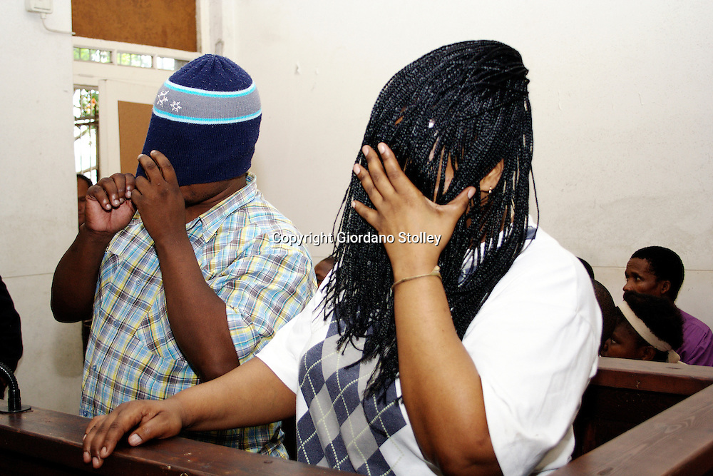 UMZINTO - 22 January 2008 - Thozamile Taki, 36 (left), and his co-accused Hlengiwe Nene hide their faces from the glare of the media in the Umzinto Magistrates Court. Taki is accused of being the mastermind in the case where it is alleged that he lured the ten women to Umzinto with the promise of employment and then murdered them..It is believed that he also raped them..Picture: Giordano Stolley/Allied Picture Press
