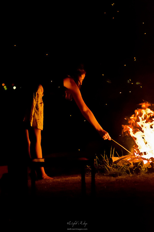 A young lady stirs the camp fire at a summer party on the banks of the Delaware River.