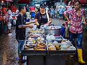 08 JUNE 2017 - BANGKOK, THAILAND: A food vendor serves a customer in Khlong Toey Market, Bangkok's main fresh market. Thai consumer confidence dropped for the first time in six months in May following a pair of bombings in Bangkok, low commodity prices paid to farmers and a sharp rise in the value of the Thai Baht versus the US Dollar and the EU Euro. The Baht is surging because of political uncertainty, related to Donald Trump, in the US and Europe. The Baht's rise is being blamed for a drop in Thai exports. This week the Baht has been trading at around 33.90 Baht to $1US, it's highest point in two years.      PHOTO BY JACK KURTZ
