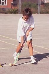 Secondary school girl playing hockey,
