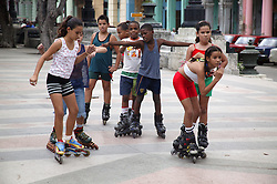 Schoolchildren rollerblading on the Paseo del Prado; Havana,