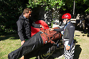 Fernado (l) loading his kiteboard onto custom racks on the side of his BMW GS motorcycle while Alfonso (red helmet) watches.
