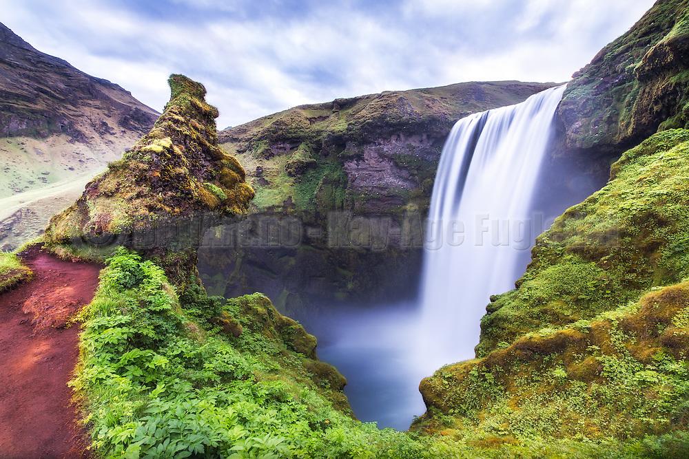 Skógafoss is a 25 m widt and 60 m high waterfall, around 5 km west of Skógar and south of Eyjafjallajökull on South-Iceland. The waterfall, which is one of the most beautiful, was protrcted in 1987. A legend says that the settler Þrasi Þórólfsson hid a gold coffin behind the waterfall | Skógafoss er et 25 m bredt og 60 m høgt fossefall ca. 5 km vest for Skógar og sør for Eyjafjallajökull på Sør-Island. Fossen som er en av Islands vakreste, ble fredet i 1987. Sagnet sier at landnåmsmannen Þrasi Þórólfsson gjemte en gullkiste bak fossen.