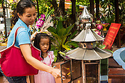 04 JANUARY 2012 - BANGKOK, THAILAND:  A woman and her daughter pray at shrine to Guanyin, the Chinese Goddess of Mercy on the grounds of Wat Mahabut in eastern Bangkok. Guanyin is a popular figure in Thai Buddhism. The temple was built in 1762 and predates the founding of the city of Bangkok. Just a few minutes from downtown Bangkok, the neighborhoods around Wat Mahabut are interlaced with canals and still resemble the Bangkok of 60 years ago. Wat Mahabut is a large temple off Sukhumvit Soi 77. The temple is the site of many shrines to Thai ghosts. Many fortune tellers also work on the temple's grounds.   PHOTO BY JACK KURTZ