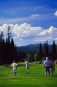 Golfers at McCalls Spring Meadows golf course with Bundage Mountain in the Background. Idaho. Editorial Use Only.