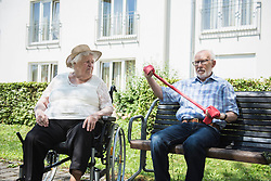 Senior woman and man exercising with resistance band at rest home garden, Bavaria, Germany, Europe