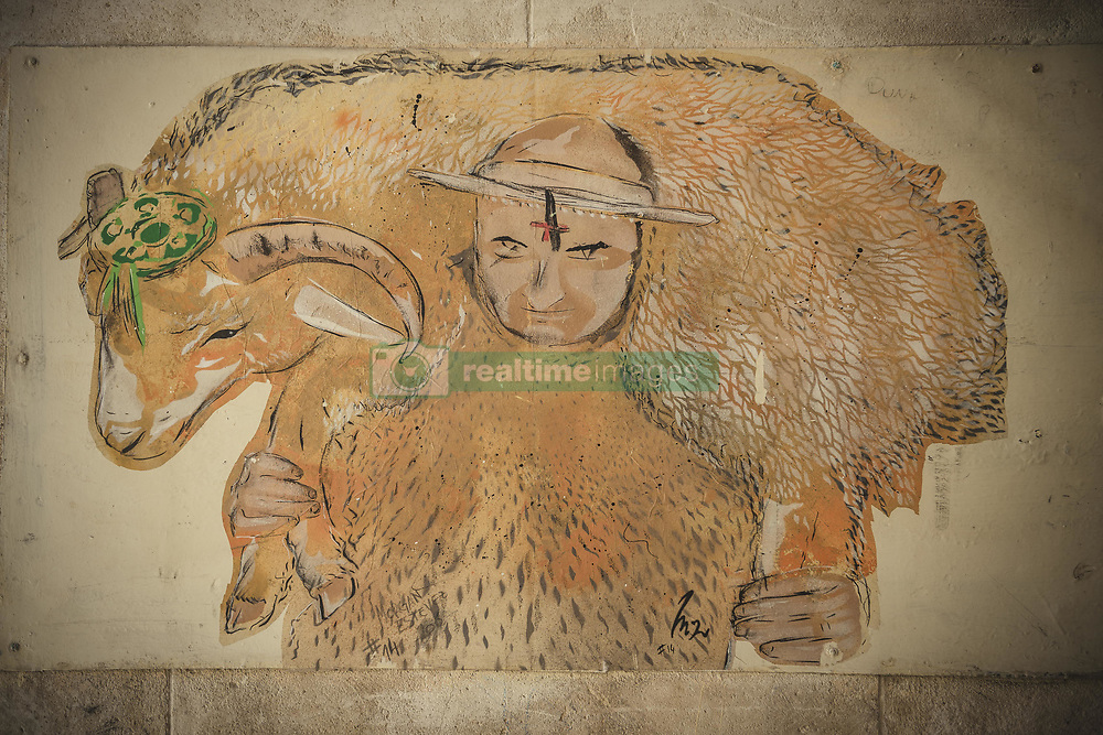 June 18, 2017 - Ciutadella De Menorca, Balearic Islands, Spain - A graffiti shows the 's'Homo des Be' (sheepman), a young man clad in a sheepskin, carrying a live ram around his shoulders as he spends the Sunday before Ciutadella's Saint John festival walking barefoot through the ancient city quarters accompanied by a Saint John committee making frequent stops at many houses. (Credit Image: © Matthias Oesterle via ZUMA Wire)