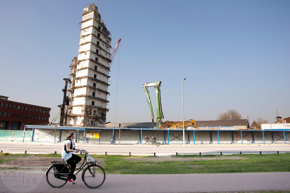 Een meisje fietst voorbij een toren die gesloopt wordt.<br /> <br /> A girl on a bike is passing a throw-downed tower.