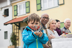 Little boy holding forks in his hands and his family waiting for him, Bavaria, Germany