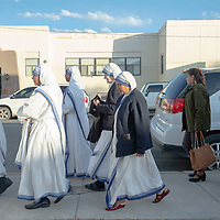 Sisters from the Our Lady-Guadalupe Parrish, walk east down Wilson Ave. to attend the blessing ceremony for the new San Damiano Hall in Gallup Friday.